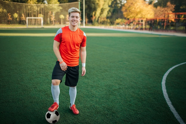 Leuke en goed gebouwde sporter staan en poseren op camera. hij houdt een voet op de bal. guy ziet er zelfverzekerd uit. hij staat op het gazon.