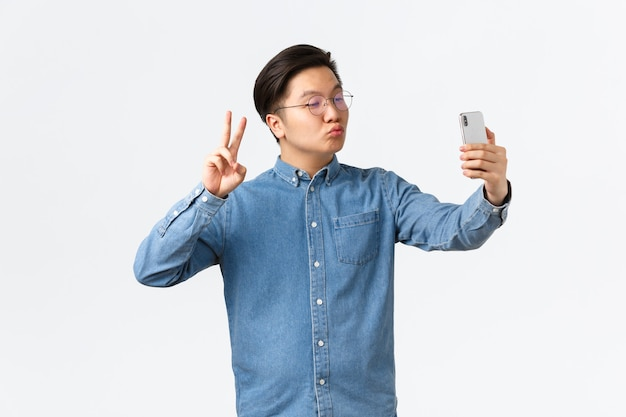 Leuke en grappige aziatische jonge kerel die dom pruilt, selfie neemt op smartphone, fotofilter-app gebruikt om van uiterlijk te veranderen, zichzelf neerschiet met vredesteken en kus, witte achtergrond.