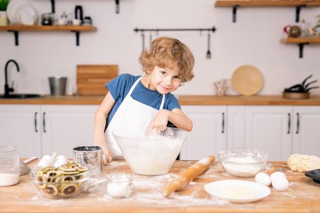 Leuke en grappige kleine jongen die in kom met bloem richt terwijl het ei gaat breken om deeg voor gebak te maken