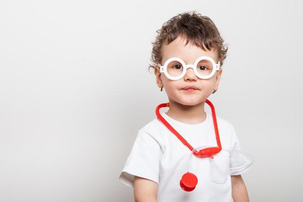 Leuke en grappige krullende peuter in een dokterskostuum met een stethoscoop om zijn nek en in de bril van hun kinderen dokter speelgoed set.