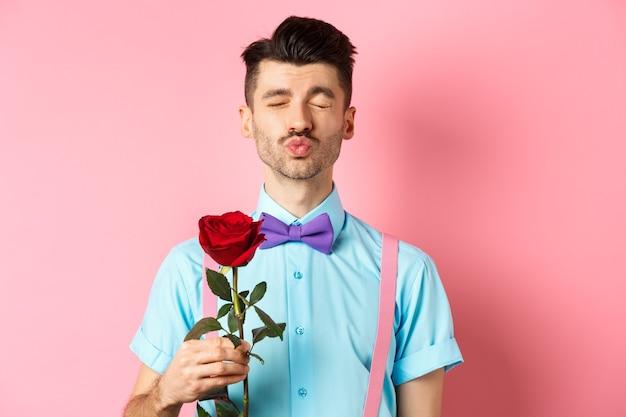 Leuke en grappige man wacht op kus van minnaar op valentijnsdag, met mooie rode roos voor vriendin, staande over roze achtergrond.