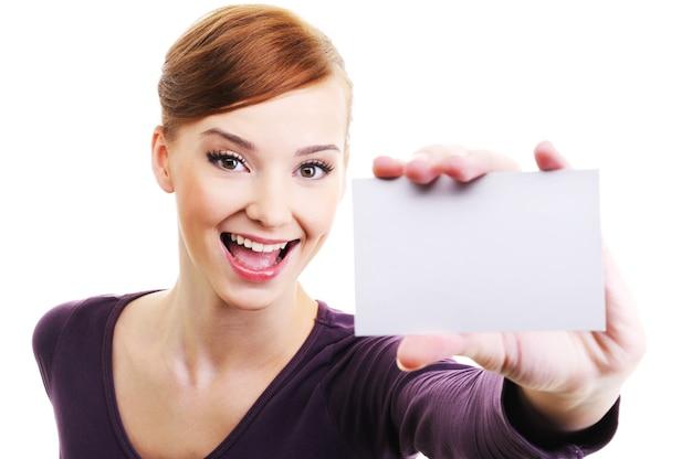 Leuke en lachende mooie vrouwelijke persoon met blanco visitekaartje in de hand. hoge kijkhoek