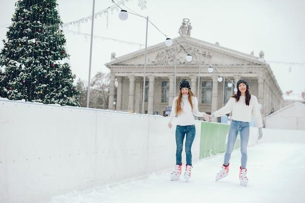 Leuke en mooie meisjes in een witte trui in een winterstad