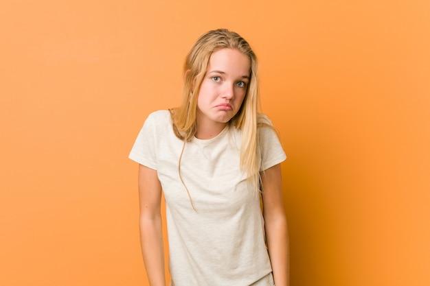 Leuke en natuurlijke tiener vrouw haalt schouders en verwarde ogen op.