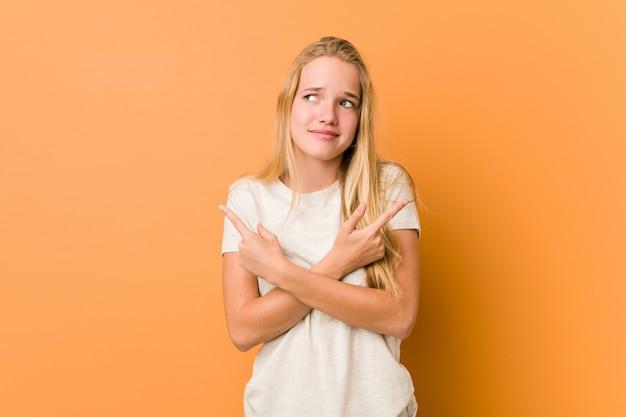 Leuke en natuurlijke tiener vrouw wijst zijwaarts, probeert te kiezen tussen twee opties.