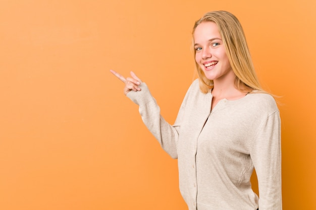 Leuke en natuurlijke tienervrouw die vrolijk het richten met weg wijsvinger glimlachen.