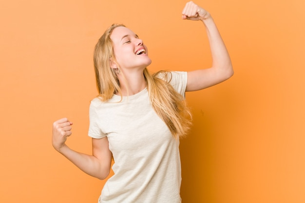 Leuke en natuurlijke tienervrouw die vuist opheft na een overwinning, winnaarconcept.