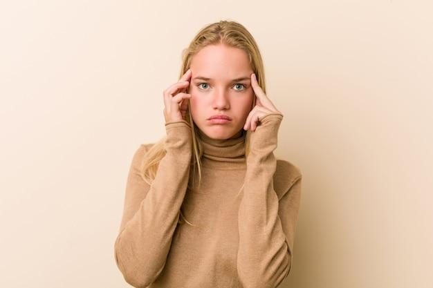 Leuke en natuurlijke tienervrouw gericht op een taak, waarbij wijsvingers hoofd houden.