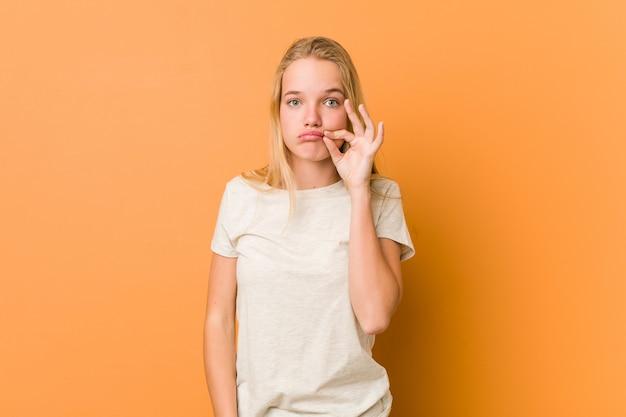 Leuke en natuurlijke tienervrouw met vingers op lippen die een geheim houden.