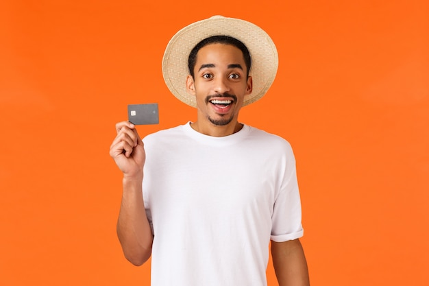 Leuke en opgewonden afro-amerikaanse man kocht reisvakantie voor vakantie met kredietgeld, kaart vasthouden en glimlachen geamuseerd, zijnde premium klantbank die vip-terminal luchthaven zit, oranje muur