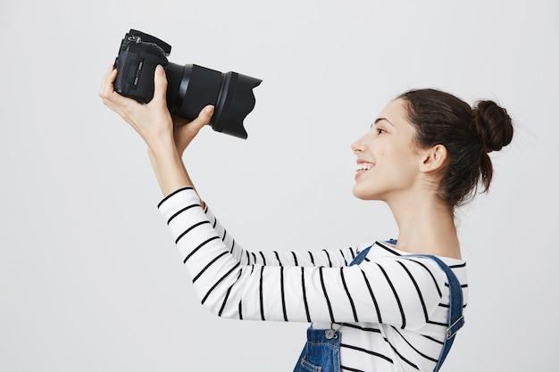 Leuke en opgewonden meisjesfotograaf die selfie op professionele camera neemt