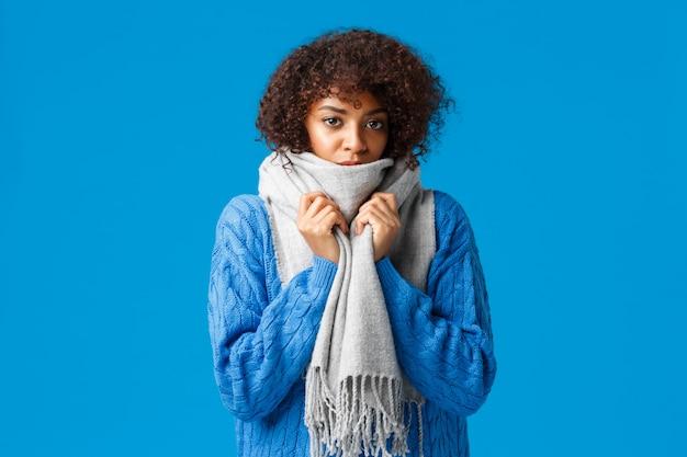 Leuke en sombere jonge afro-amerikaanse mooie vrouw met afro-kapsel, omhult zichzelf met warme sjaal, voelt koud of koud aan in de winter, staat blauwe muur, wacht op iemand die de verwarming verhit