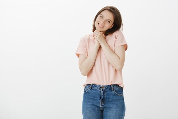 Leuke en tedere, schattige jonge vrouw die een gek gezicht trekt, een geschenk of een compliment krijgt