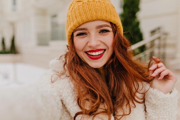 Leuke europese dame die van de winter geniet. vrolijk gember meisje in witte jas selfie buiten maken.