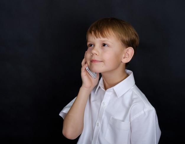 Leuke europese jongen die graag op een mobiele telefoon praat. isoleren op een zwarte