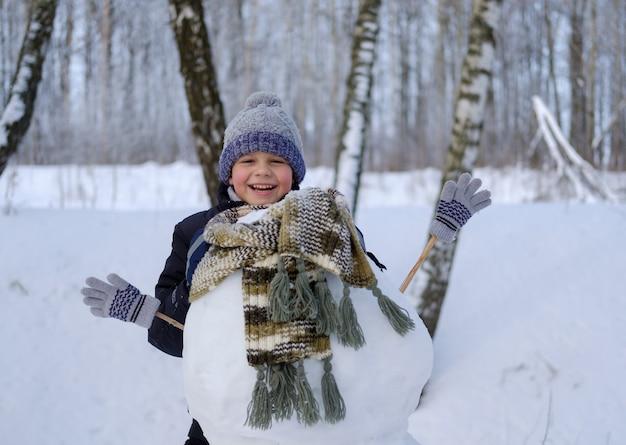 Leuke europese jongen en de grappige sneeuwpop in het besneeuwde bos op een winterse dag in de sneeuw