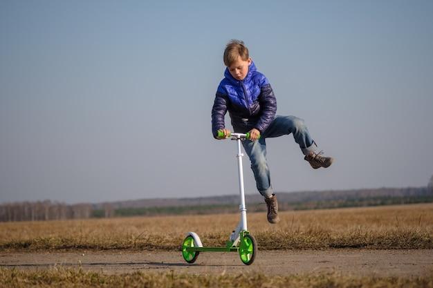 Leuke europese jongen rijden en trucs doen op scooter tijdens het lopen