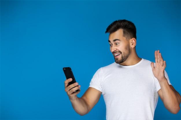 Leuke europese man glimlacht naar de telefoon en zwaait met zijn hand