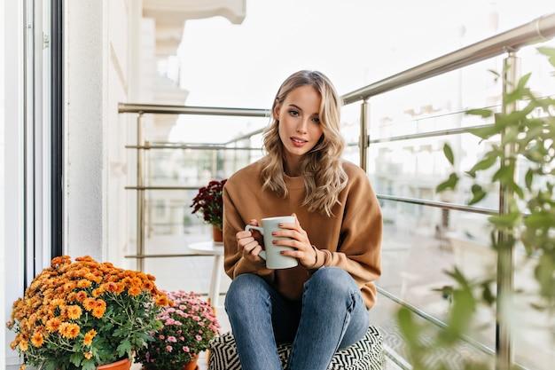 Leuke europese vrouw die thee drinkt op terras. portret van geïnteresseerd blond meisje dat van koffie geniet.