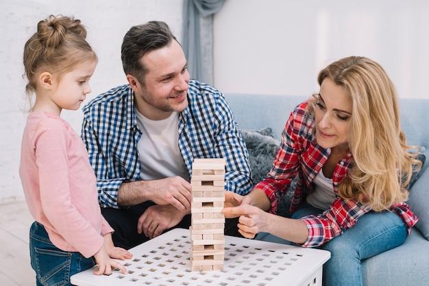 Leuke familie die de houten toren van het blokspel thuis spelen