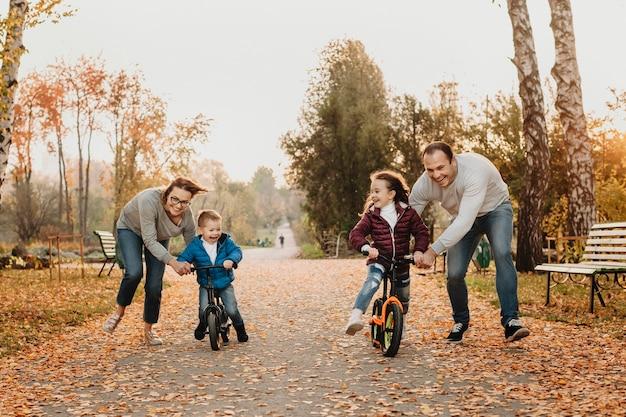 Leuke familie die met hun kinderen speelt terwijl ze hen leren fietsen in het park.
