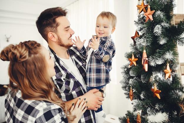 Leuke familie die zich dichtbij kerstboom bevindt