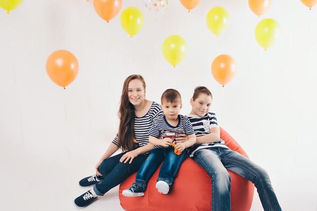 Leuke familie op het feest. kinderen op een witte achtergrond tussen de gekleurde ballen vieren hun verjaardag