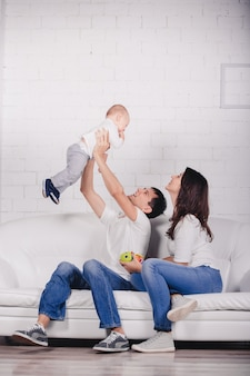 Leuke familie op studio achtergrond in licht, modern interieur binnenshuis. glimlachende jonge moeder en vader met kindzoon die samen stellen en op bank zitten.