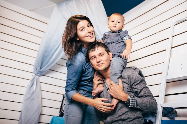 Leuke familie op studio achtergrond in licht, modern interieur binnenshuis. glimlachende jonge moeder en vader met kindzoon die samen stellen.