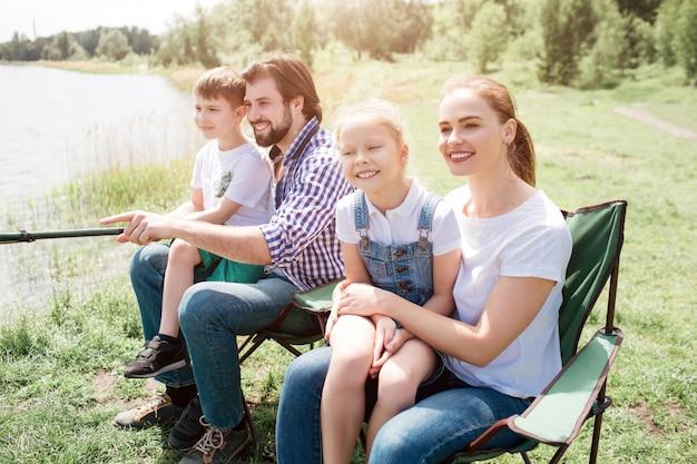 Leuke familiefoto van vier mensen die samen vis vangen. klein meisje zit op haar moeders schoot terwijl kleine jongen hetzelfde doet, maar op de schoot van zijn vader. jongens houden vishengel samen.