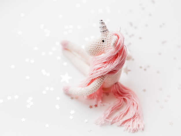 Leuke fee-eenhoorn met roze manen en een staart gemaakt van draden.