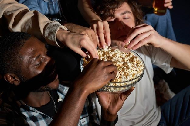 Leuke film met vrienden. groep mensen die popcorn eten tijdens het kijken naar film op tv, thuis, popcorn uit de kom nemen, genieten van het weekend. bovenaanzicht