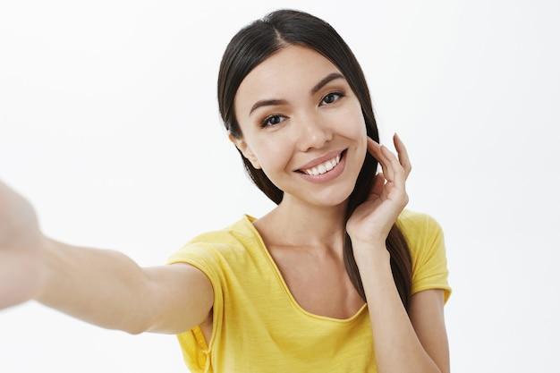Leuke foto maken om geliefde te sturen. charmant aantrekkelijk en teder meisje flikkend haarstreng flirterig kantelend hoofd,