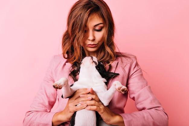 Leuke franse buldog die omhoog gembervrouw bekijkt. binnen schot van enthousiaste krullende vrouw met haar puppy.