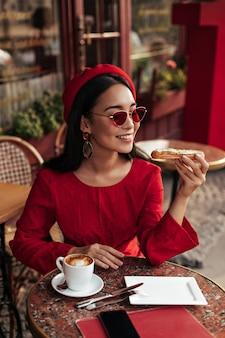 Leuke gebruinde brunette vrouw in stijlvolle rode jurk, baret en zonnebril zit in café