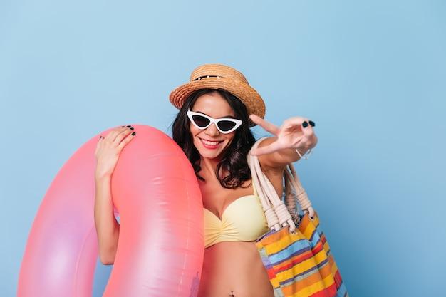 Leuke gelooide vrouw die in zonnebril vredesteken toont