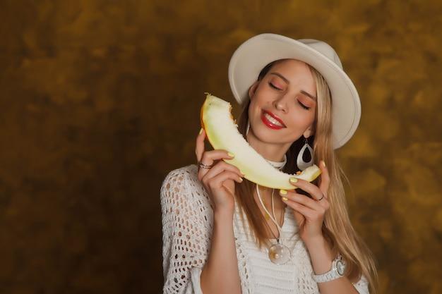 Leuke gelukkig stijlvol geklede lachende jonge vrouw met meloen in hoed op gouden achtergrond ziet er tevreden uit, gelukkig. concept van een emotioneel portret. auteursrechtruimte