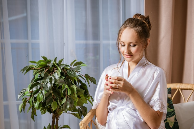 Leuke gelukkig zwangere vrouw in een witte jas op de negende maand van de zwangerschap, zittend in een stoel met een mok in haar hand.