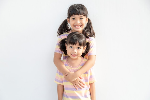 Leuke gelukkige aziatische broers en zussen knuffelen knuffelen gevoel liefde en verbinding, lachende jongen meisje zus omarmen kleine meisje zus op witte achtergrond, 2 kinderen goede relaties