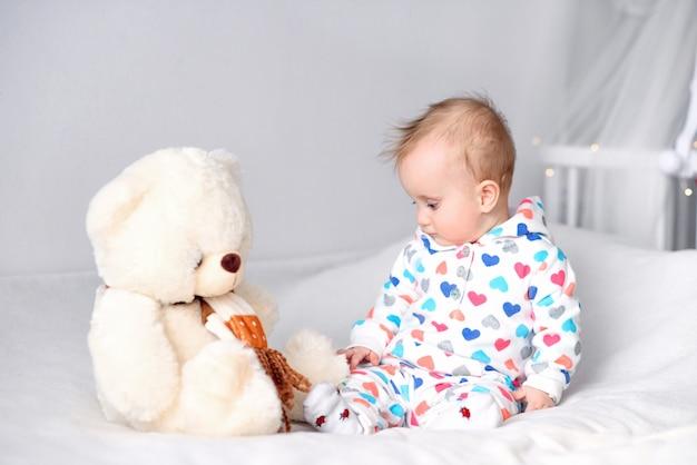 Leuke gelukkige baby in een modieuze hoodiezitting op een witte deken bij het bed en het spelen met haar teddybeer