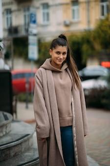 Leuke gelukkige glimlachende brunette die door de stad loopt