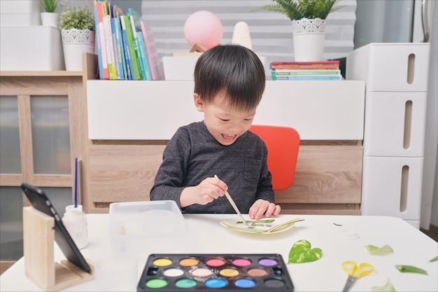 Leuke gelukkige glimlachende kleine aziatische peuterjongen geniet van het gebruik van lijm die thuis kunsten doet