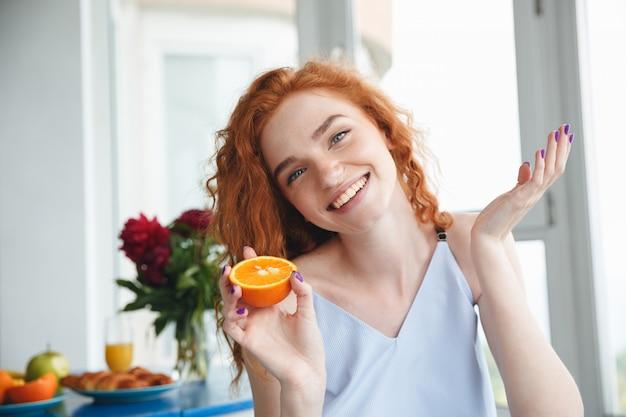 Leuke gelukkige jonge roodharigedame die dichtbij bloemen sinaasappel houdt