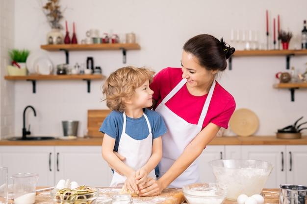 Leuke gelukkige jongen die naar zijn moeder kijkt terwijl hij haar helpt om zelfgemaakt deeg te kneden voordat ze koekjes of ander gebak maakt