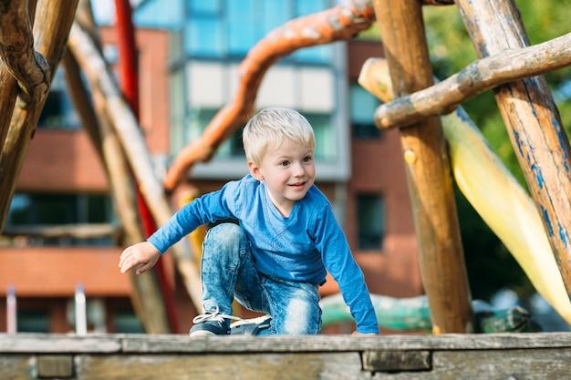 Leuke gelukkige jongen met blond haar die pret op de speelplaats op zonnige de zomerdag hebben.
