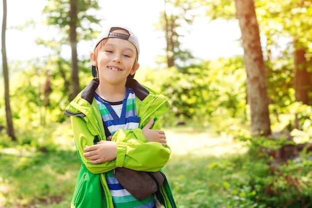 Leuke gelukkige jongen met plezier in het bos. familie kampeertijd. zomervakantie, familietijd op de natuur. kinderen wandelen in de bergen. een gelukkige en gezonde jeugd. gelukkige jongen die van een wandeling in het bos geniet.