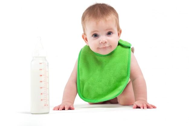 Leuke gelukkige kleine jongen in groene slab dichtbij melkfles