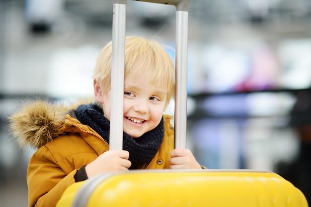 Leuke gelukkige kleine jongen met grote gele koffer op internationale luchthaven vóór de vlucht