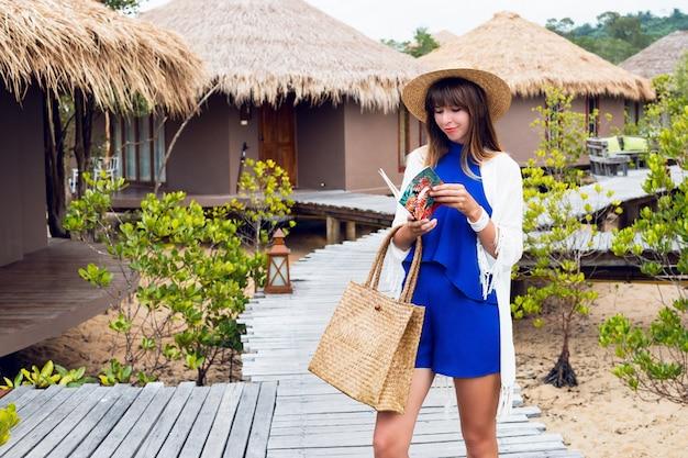 Leuke gelukkige reizende vrouw met notitieboekje glimlachend a. blauwe jumpsuit, strooien hoed en tas, zonnebril. brunette meisje poseren in haar geweldige luxevilla.