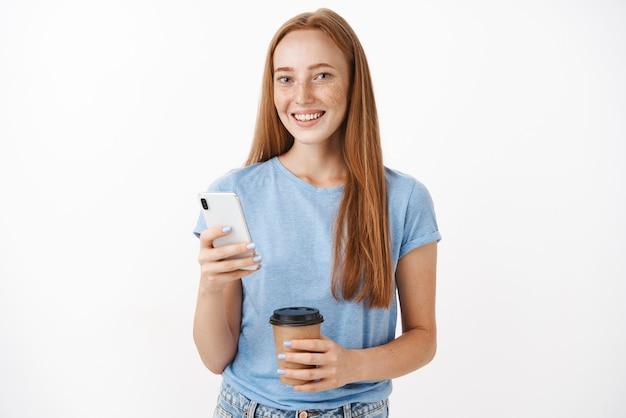 Leuke, gelukkige roodharige vrouw met sproeten lachend met kopje koffie en smartphone